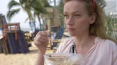 kaffir lime leaves : woman eating Thai soup Tom Yam sitting on the beach, 4k slow-motion