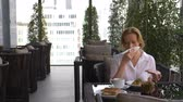 varanda : Beautiful elegant girl, having breakfast in a cafe on the terrace with a beautiful view of the skyscrapers. A woman drinking hot coffee on the hotels luxurious terrace. 4k,