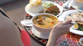 çili : prawn spicy soup is a Thai dish with sour and spicy taste. busty girl in a bikini eats Tom Yam at a table by the pool. 4k, slow-motion, close-up. concept of travel tourism