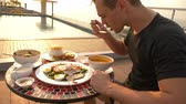 coconut soup : Shrimp soup is a Thai dish with a sour and spicy taste. the man is eating Tom Yam at a table by the pool. 4k, slow motion, close-up. concept of tourism tourism Stock Footage
