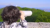 curvo : boy teenager, traveler, looking through a telescope on top of a mountain. 4k, slow motion