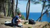 namiot : a male tourist arranges a tent on the edge of a steep coastal shore in a pine grove with a magnificent view of the seascape. 4k.