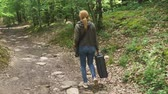 sigilo : girl, walks through the woods with a heavy black suitcase. 4k, slow-motion shooting, steadicam shot. Vídeos