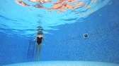 buborékok : 4k. View under water. Woman in a black swimsuit Swims in the pool.