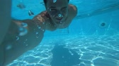 calções de banho : A young white handsome male doing an underwater selfie on an action camera. Portrait of a young man taking himself off to the camera under water. 4k Vídeos