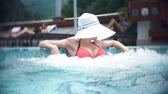 грудь : SLOW MOTION, CLOSE, PORTRAIT. young woman in a big white hat, sunbathe and relax on a sunny day in a luxurious pool on a background of a mountain landscape. mountain resort with outdoor pool. 4k