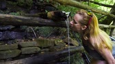 pó : The woman curves to quench her thirst. Drinking water from the mountain. clean source. 4k, slow motion Vídeos