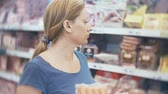 полка : woman buys a sausage in a supermarket, 4k Стоковые видеозаписи
