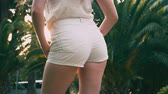 bunda : Beautiful young woman with long blond hair, in white short shorts. In the background there are tall palm trees. sun glare. the woman moves her hips. 4k, slow motion.