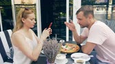 seitensprung : couple in an outdoor cafe. Man and woman on a date. one partner looks at his phone, the second tries to talk to him. 4k, slow motion.