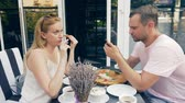 adversidade : couple in an outdoor cafe. Man and woman on a date. one partner looks at his phone, the second tries to talk to him. 4k, slow motion.