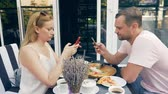 rozvod : couple in an outdoor cafe. Man and woman on a date. one partner looks at his phone, the second tries to talk to him. 4k, slow motion.