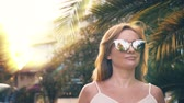 visszaverődés : Beautiful stylish blond woman in sunglasses , walking along a palm tree path. The palm is reflected in the glasses. 4K slow motion.