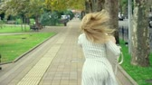 잃다 : woman blonde is talking on the phone on the run, she is in a hurry. outdoors in summer. slow-motion