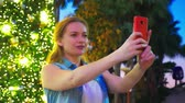 písek : happy woman on the background of the Christmas tree and palm trees in a tropical city. The concept of New Years travel to warm countries. using the phone Dostupné videozáznamy