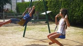 recessão : boy and girl teenager swinging on a swing with bare feet on the green lawn of the backyard of his house