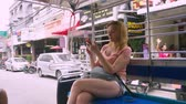 クイック : Thailand, Pattaya, Jomtien Beach, 07. 12. 2018. A beautiful young woman rides in a tuk-tuk in the afternoon and uses a smartphone. tourism concept