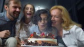 mama : Happy smiling boy blowing candles on her birthday cake. children surrounded by their family. birthday cake with candles Wideo