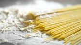 ангельский : raw pasta cappellini, closeup lie in white flour on a wooden table
