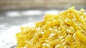 mercadoria : raw pasta fusilli, closeup lie in white flour on a wooden table. Vídeos