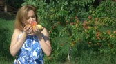 абрикос : A woman holds an armful of fresh peaches in a peach orchard amid fruit trees. and enjoys the flavor of peaches.