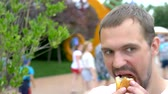 겨자 : young man eating an appetizing hotdog sitting in the park on the background of walking people, blurred background. 무비클립