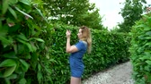решить : A woman in a short denim jumpsuit walking through a hedge maze on a sunny summer day. back view