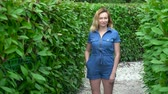 indeciso : A woman in a short denim jumpsuit standing in the middle of a hedge maze on a sunny summer day. Looks at the camera. Archivo de Video