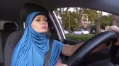 serio : beautiful muslim woman in blue hijab driving a car. rides during the day on the streets of the city.