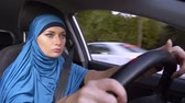운전사 : beautiful muslim woman in blue hijab driving a car. rides during the day on the streets of the city.