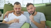 palacz : Gay couple smokes a hookah, sitting in the gazebo on the street on a sunny summer day.