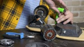 aanpassing : close-up.Man hands who repair a broken electric skateboard. unscrews the wheels Stockvideo