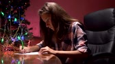 teen girl sits at a table near a decorated Christmas tree and writes a Christmas letter to Santa Claus