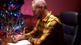 a man sits at a table near a decorated Christmas tree and writes a New Year letter to Santa Claus