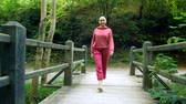 lesbian : bald woman walks on a wooden bridge in the forest. The concept of transition in life.