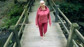 bald woman walks on a wooden bridge in the forest. The concept of transition in life.