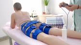selülit : the girl lies on the couch and receives the procedure of myostimulation on her legs and buttocks in a beauty salon. Body care, weight loss. Stok Video