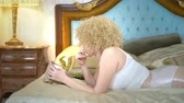 étkező : The blonde with plastic wrap on her hips and stomach lies on the bed and eats french fries, waiting for weight loss. humorous concept, weight loss.