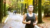 cardiologia : sporty girl with headphones Jogging in autumn Park