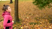 paardenstaart : Beautiful woman with long hair jogging in the autumn park. side view