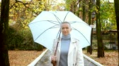 deštivý : stylish blond woman with short hair walks in the Park with umbrella Dostupné videozáznamy
