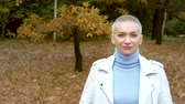 menő : stylish blond woman with very short hair walking in the autumn Park.