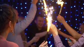 menő : group of friends celebrating at a party, lighting sparklers