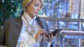 rede social : elegant stylish blond woman using mobile phone sitting in a cafe