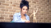manequim : beautiful brunette girl draws a sketch with a wooden mannequin Stock Footage