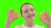 неузнаваемый : Happy girl holds half of orange near the face