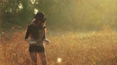 congratulação : Young girl walking in the meadow in the evening