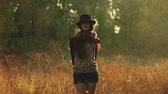 congratulação : Young girl on the meadow in the evening with a hat, looking at you Stock Footage