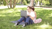 manmetro : man and woman sitting back to back in the park and working with a laptop
