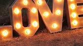 vurgulamak : Word love consisting of the letters highlighted with bulbs standing on lawn at night.